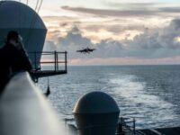 Un marinero observa un F/A-18E Super Hornet preparándose para aterrizar en la cubierta de vuelo del portaaviones USS Ronald Reagan en el Mar de China Oriental